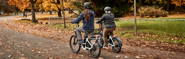 Two friends ride electric bikes from Rad Power Bikes amid fall leaves.