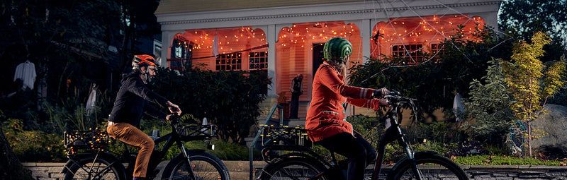 A family rides their electric bikes by a house decorated for Halloween.