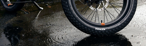 A close-up of an electric bike's fat tire on a rainy street.