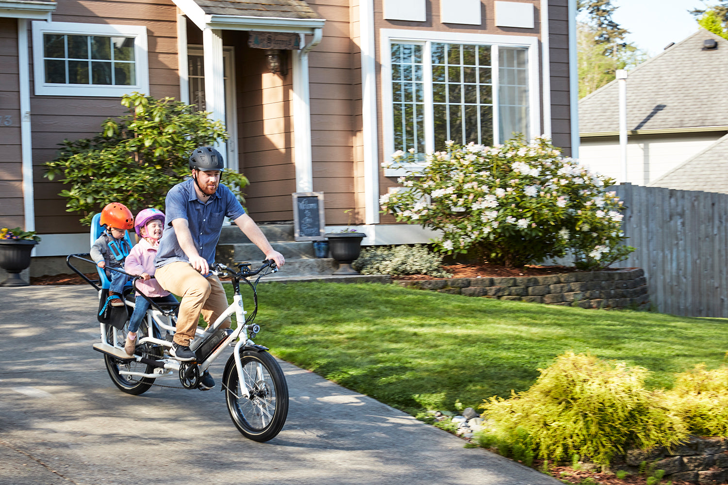 A father rides a RadWagon electric cargo bike with his children out of his driveway.