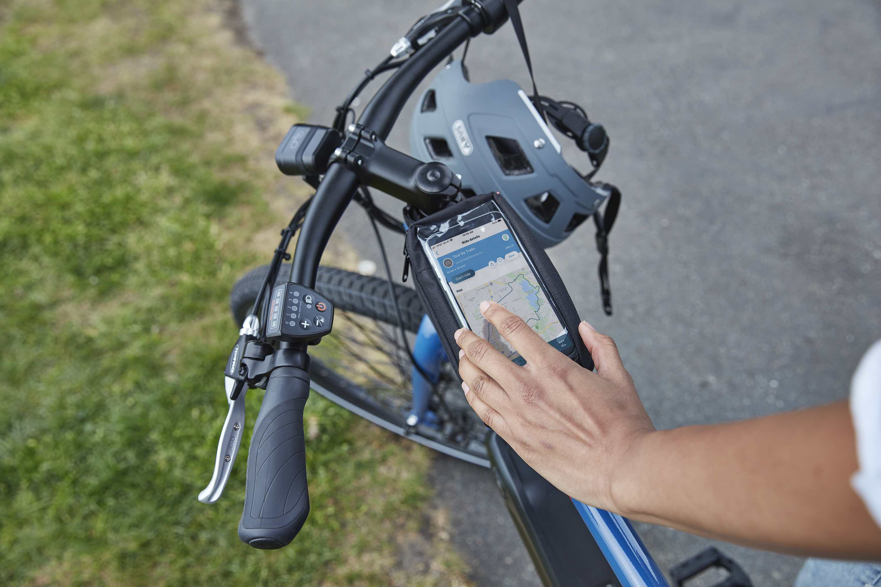 A woman looks at her Ride Spot app alongside her RadMission electric metro bike.