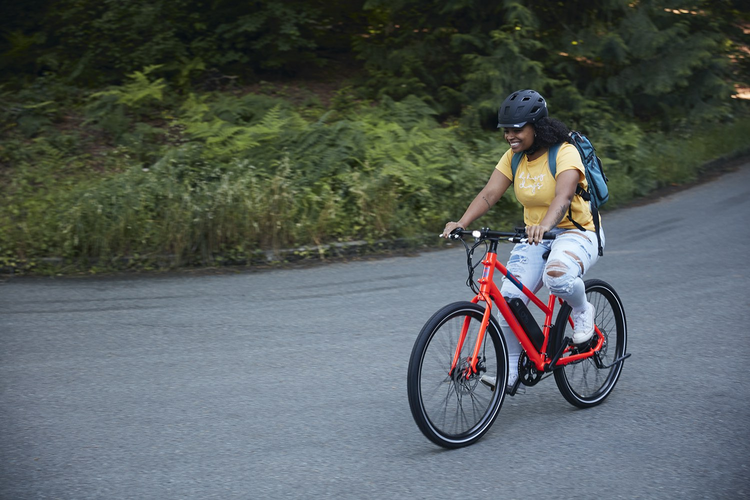 A woman smiles as she rides a red RadMission down a rural street.