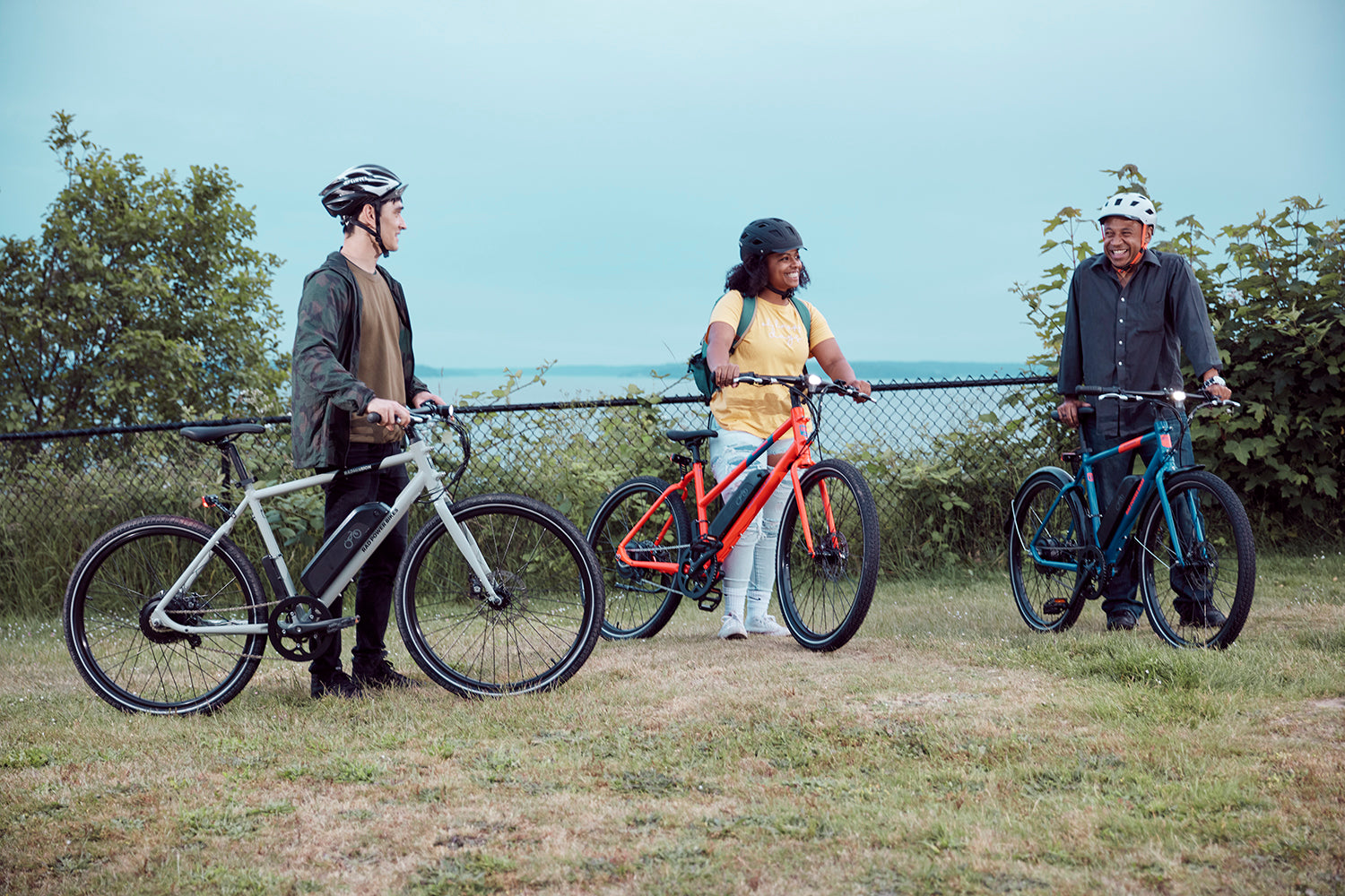 Three friends share moment after completing a ride on their RadMission electric metro bikes.