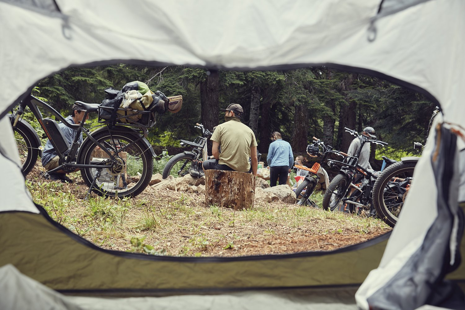 Looking outside a tent, we can see several people camping with their ebikes from Rad Power Bikes.