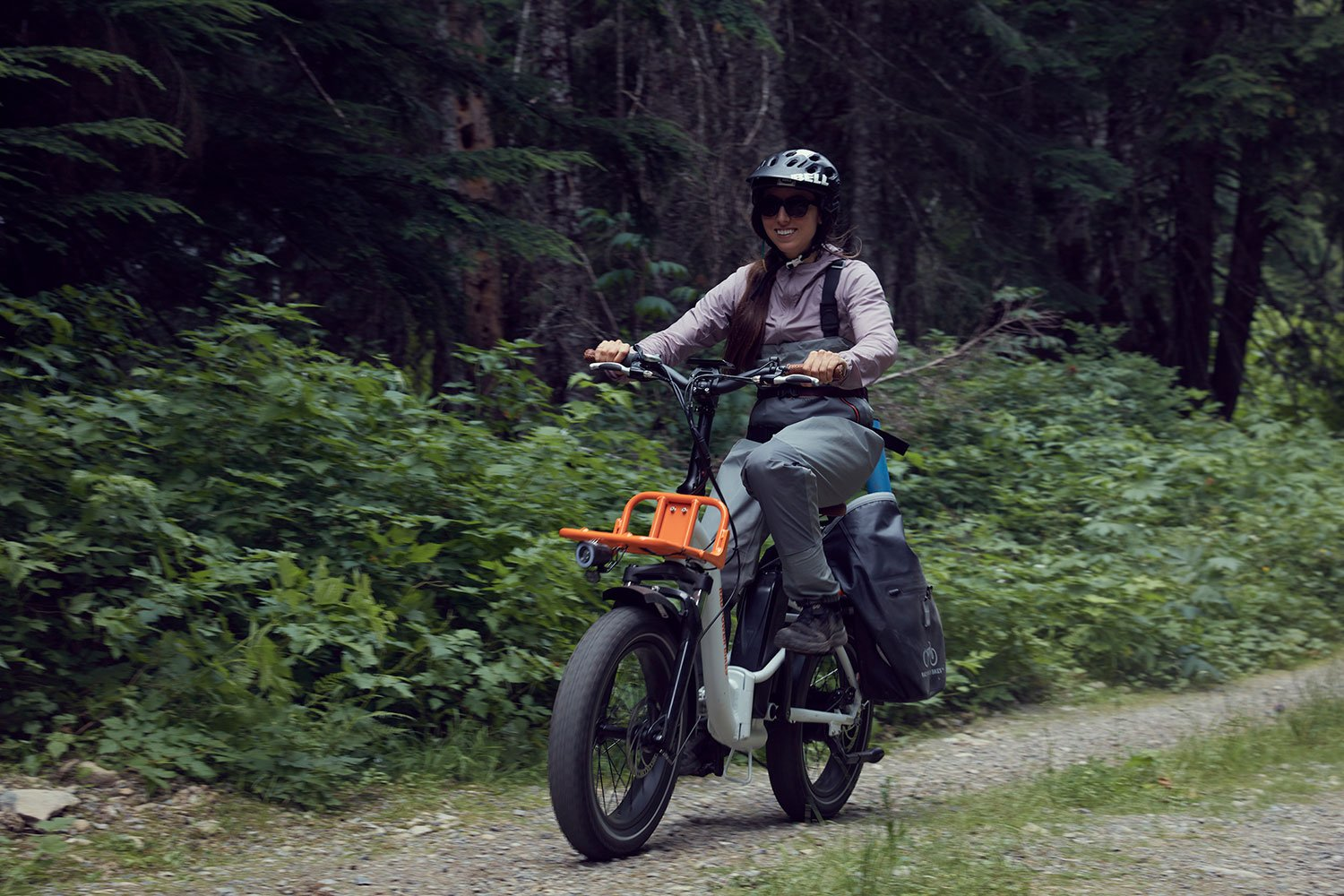 Woman riding RadMini Step-Thru on dirt road with front rack and pannier bags installed on the bike