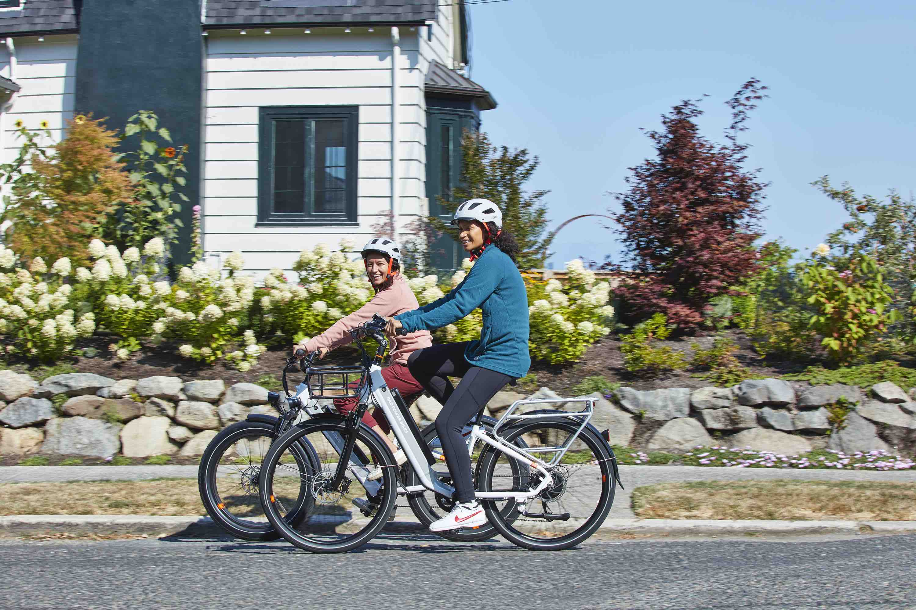 Two women ride a RadCity 5 Plus and a RadCity 6 Plus down a suburban street.