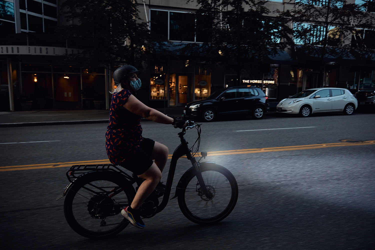 A woman rides a RadCity on an urban street at night.