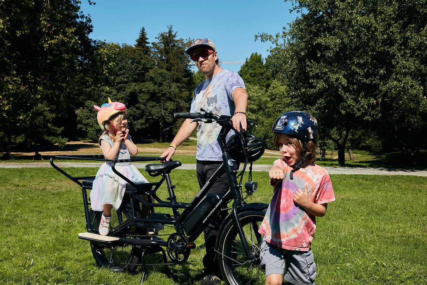A child and father stand alongside a RadWagon in a park.