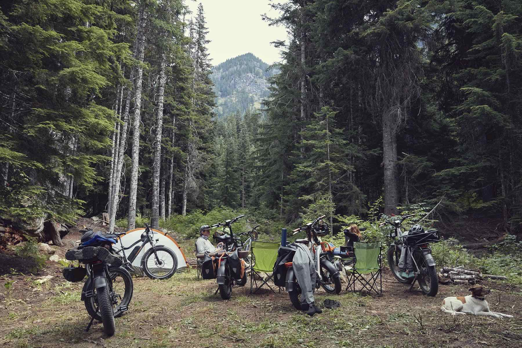 A group of people enjoying a camping trip alongside their electric bikes.