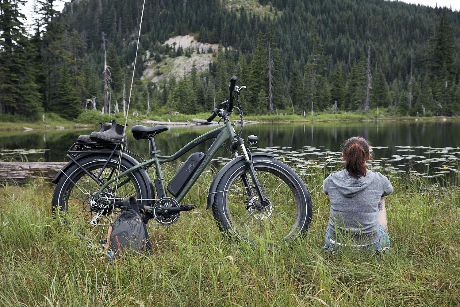 A woman sits next to a serene lake alongside her RadRover electric fat bike.