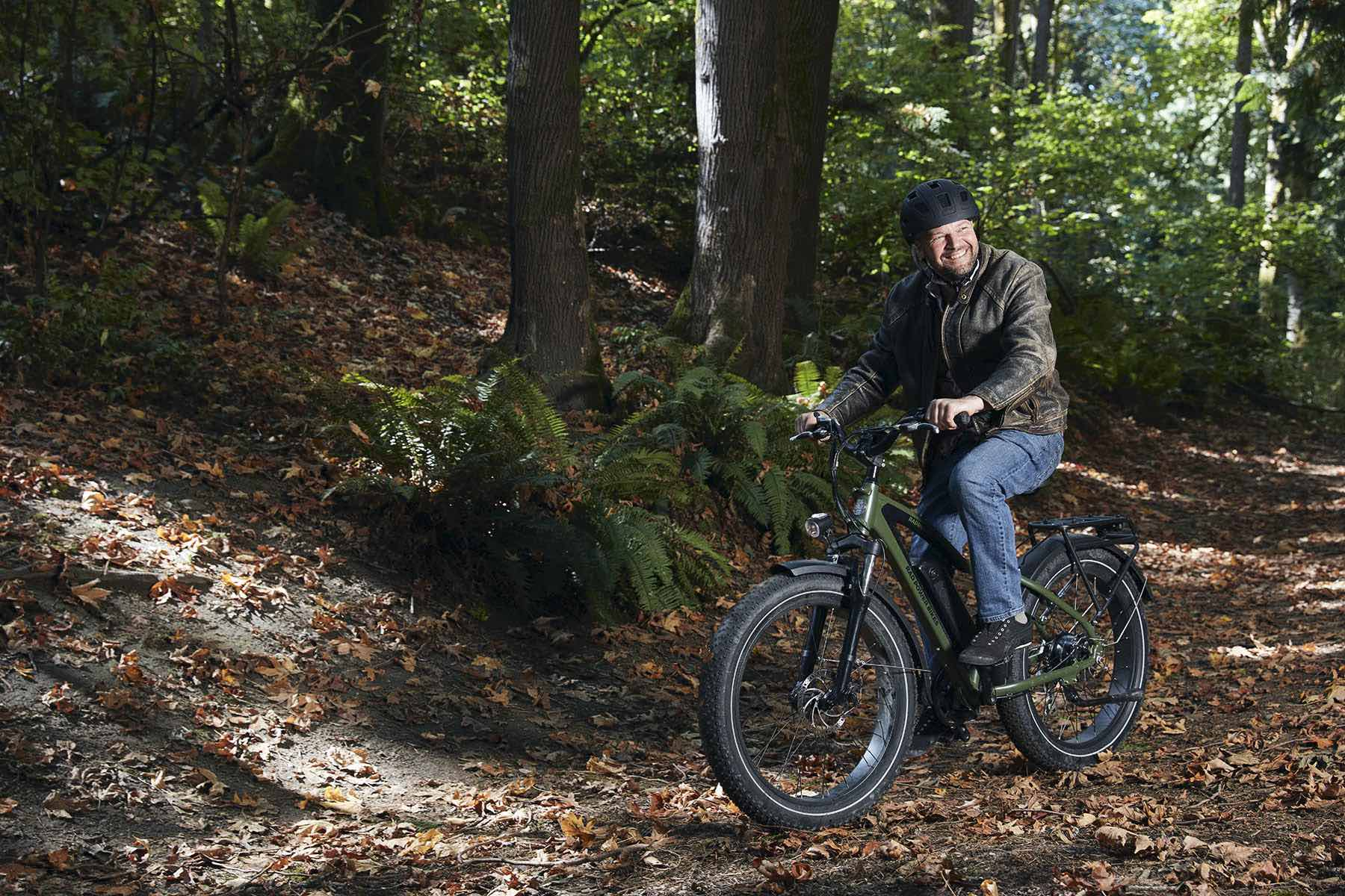 A man rides his green RadRover electric fat bike across a trail in the woods.