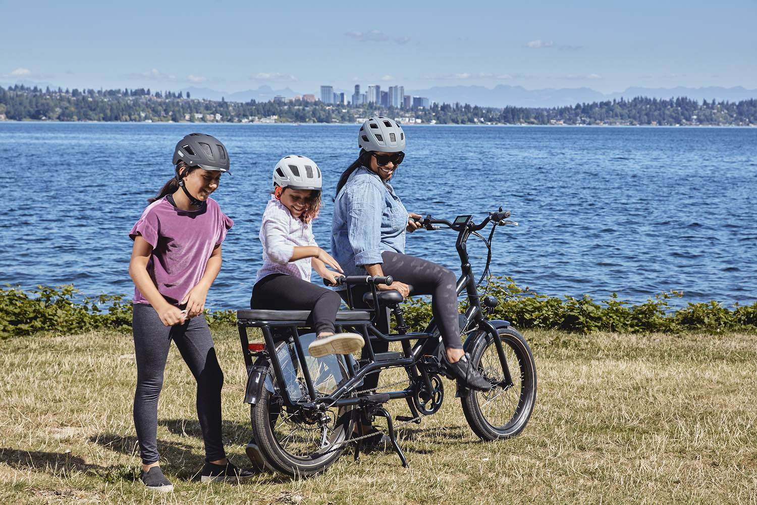 A mother and her daughters climb onto the RadWagon 4 electric cargo bike.