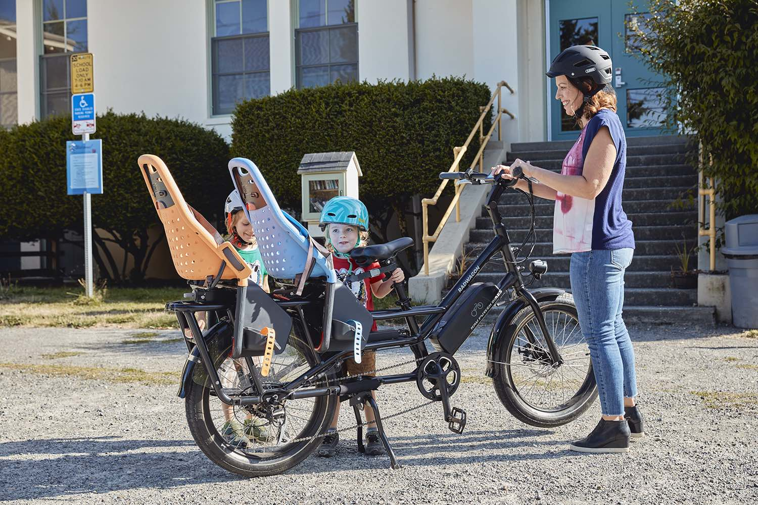 A mother picks up her two kids from school with the RadWagon 4 electric cargo bike.
