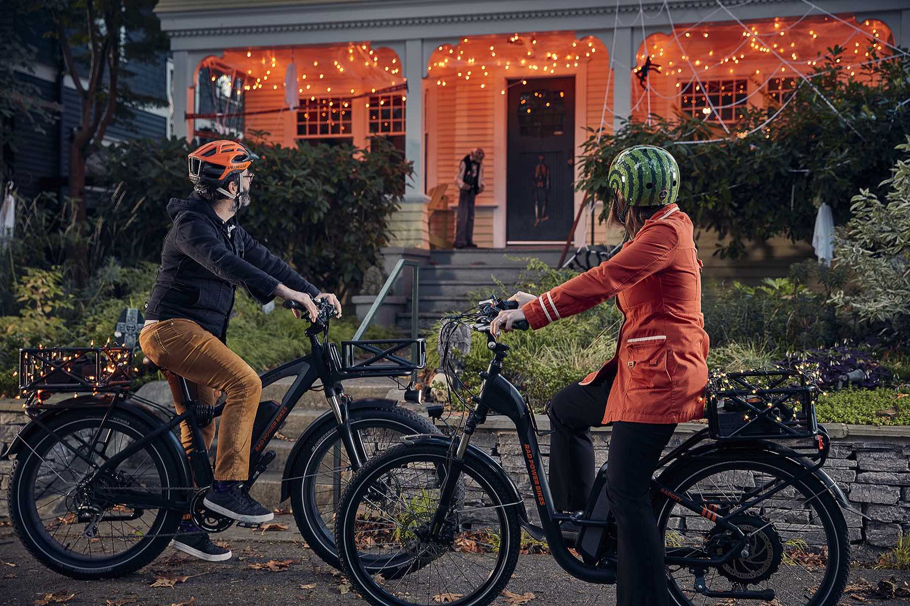 A couple rides by a house covered in Halloween decorations on their electric bikes.