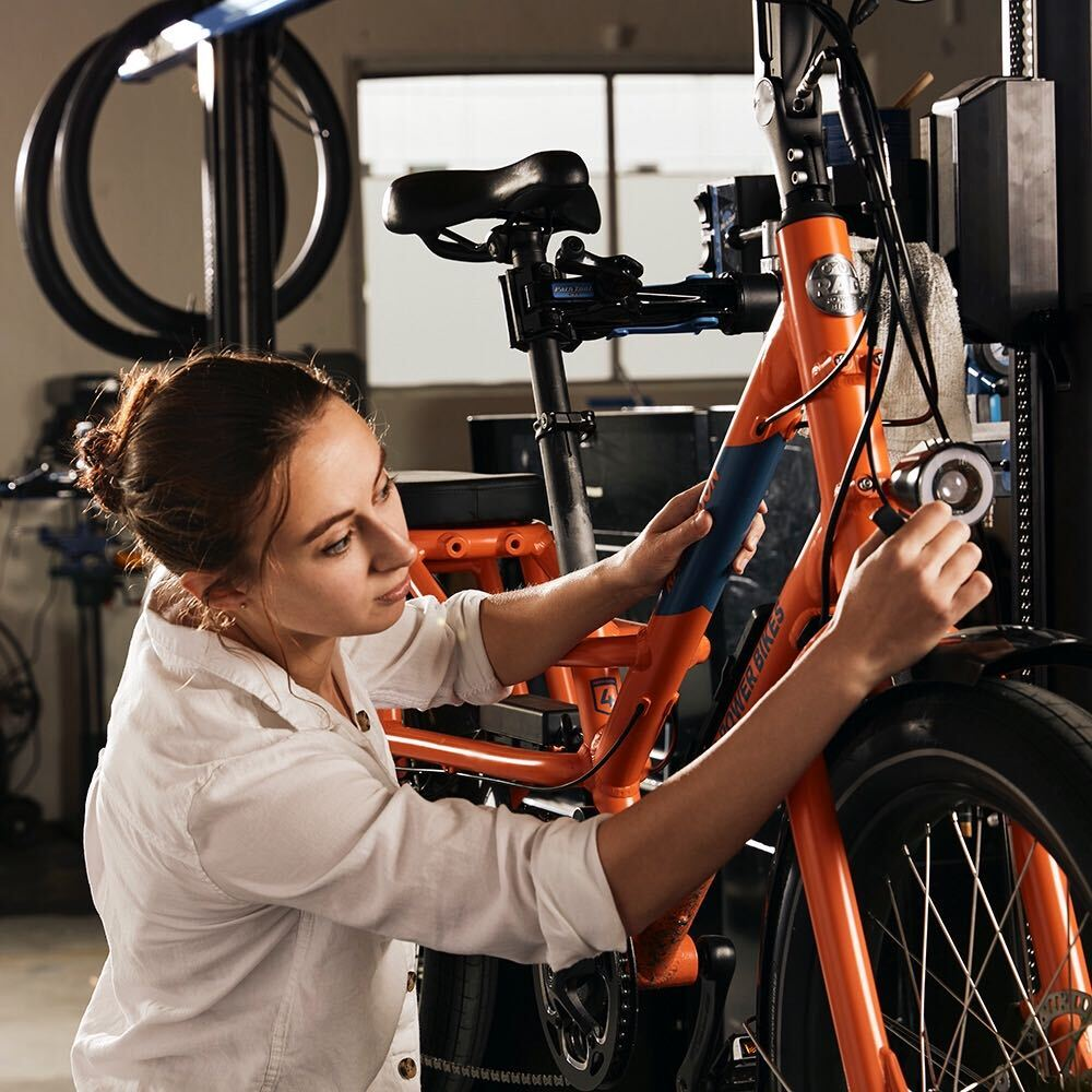 A young mechanic works on a red RadMission in a garage.