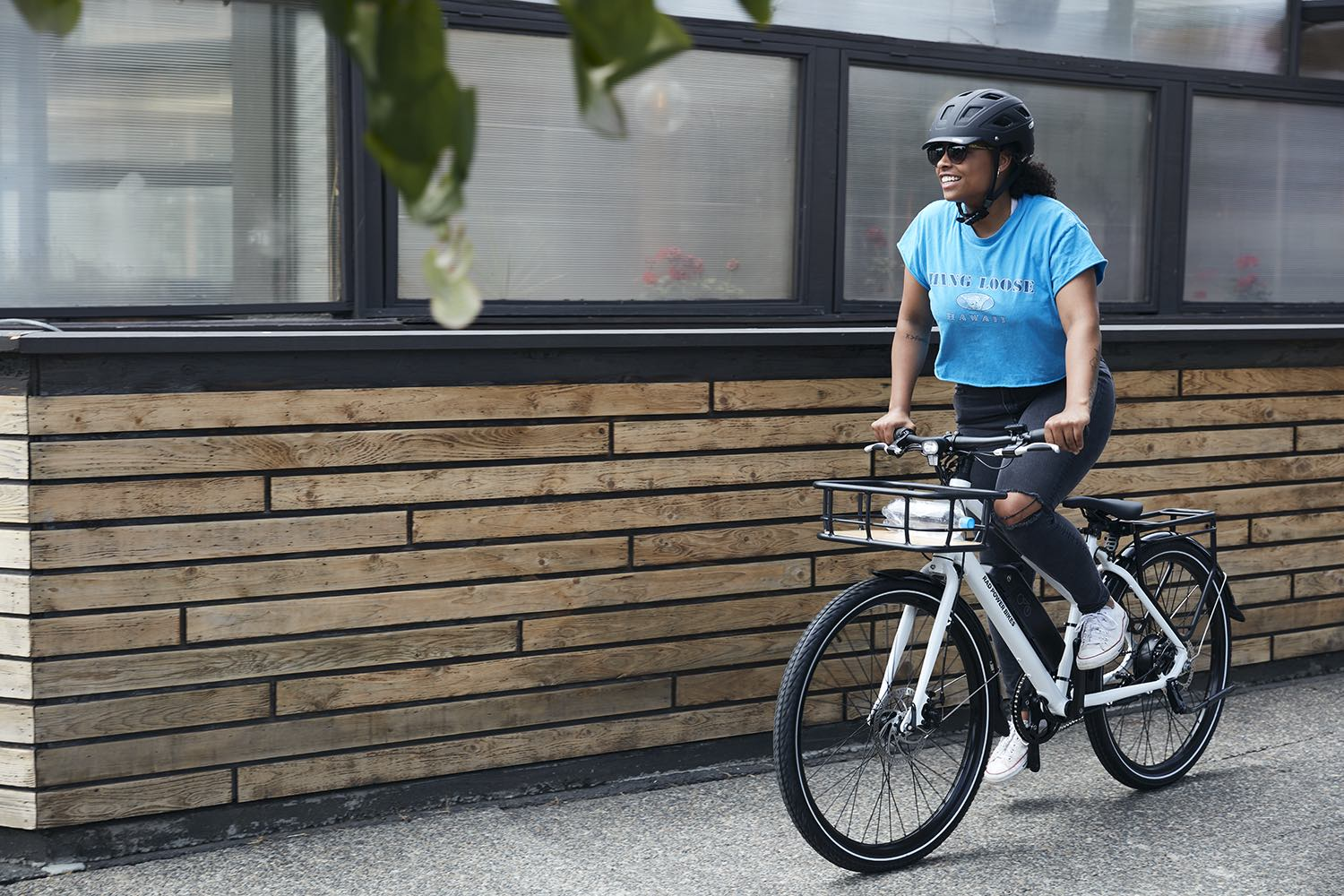 A young woman proudly walks alongside her RadMission electric metro bike.