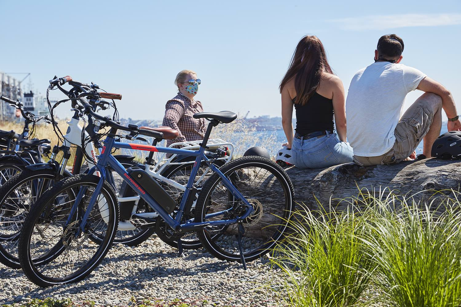 A group of friends meet along the beach, with their ebikes perched to the side.