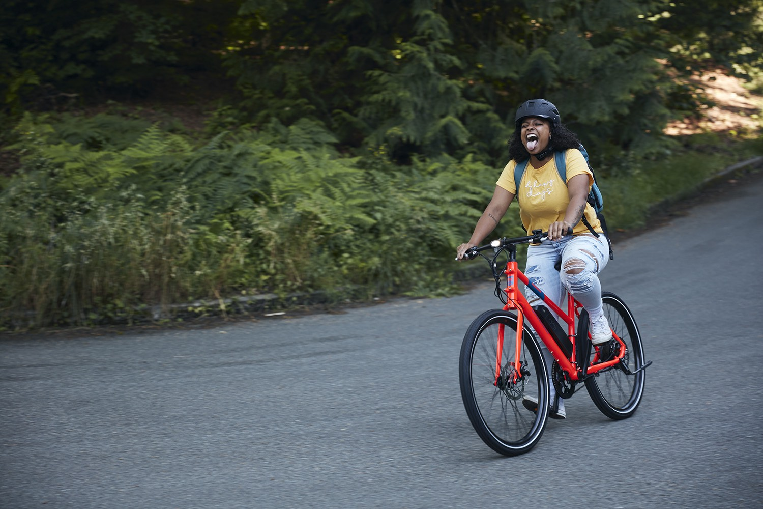A woman has fun while riding a RadMission down the street.