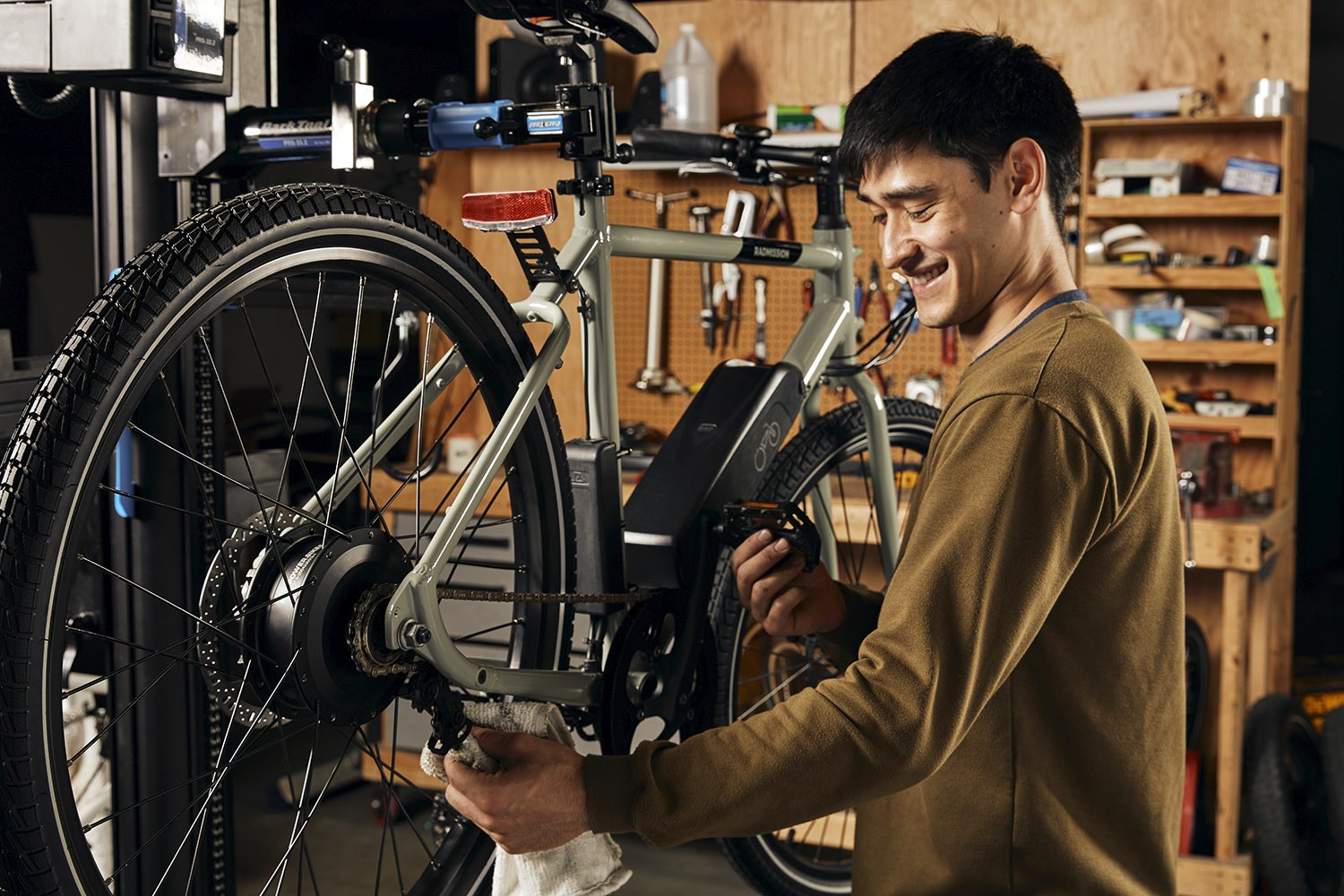 A mechanic inspects a grey RadMission electric metro bike.