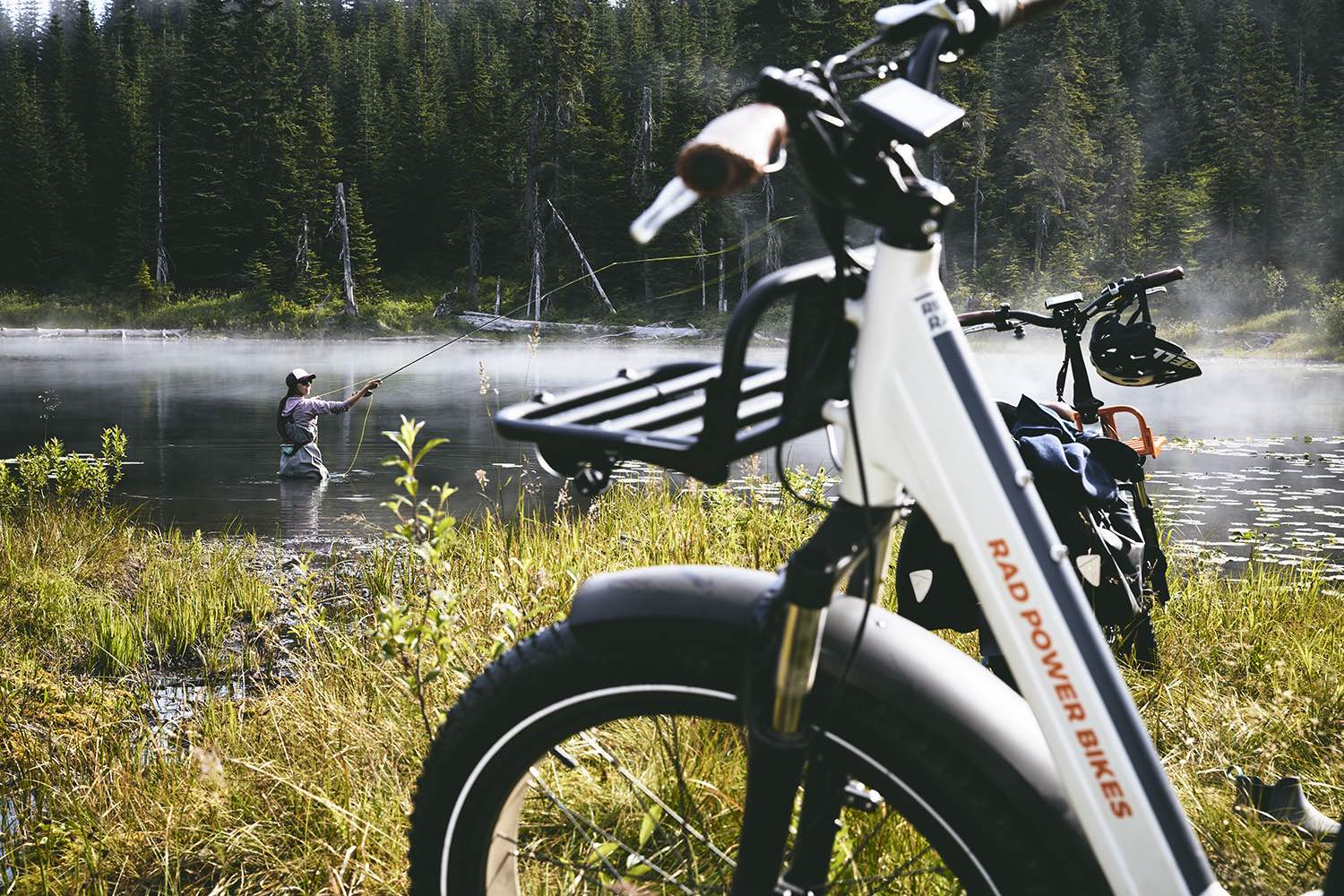A woman fishes alongside her RadRover electric fat bike.