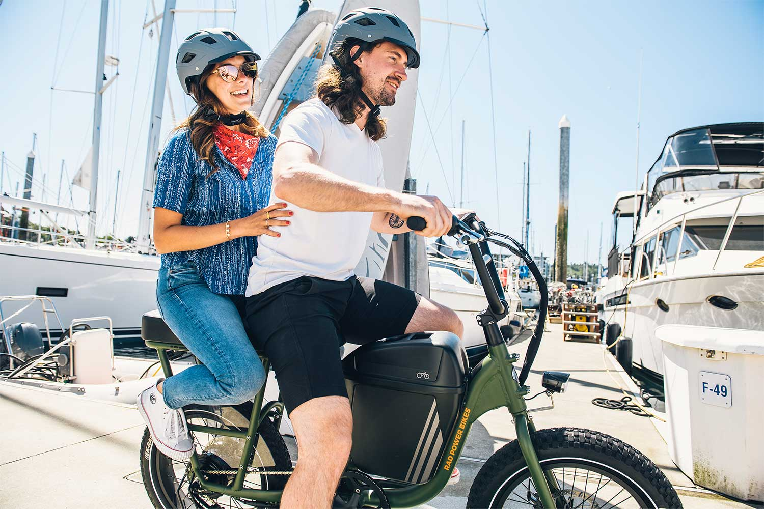 A woman and mad ride the RadRunner, 2021's best utility ebike,on. a dock.