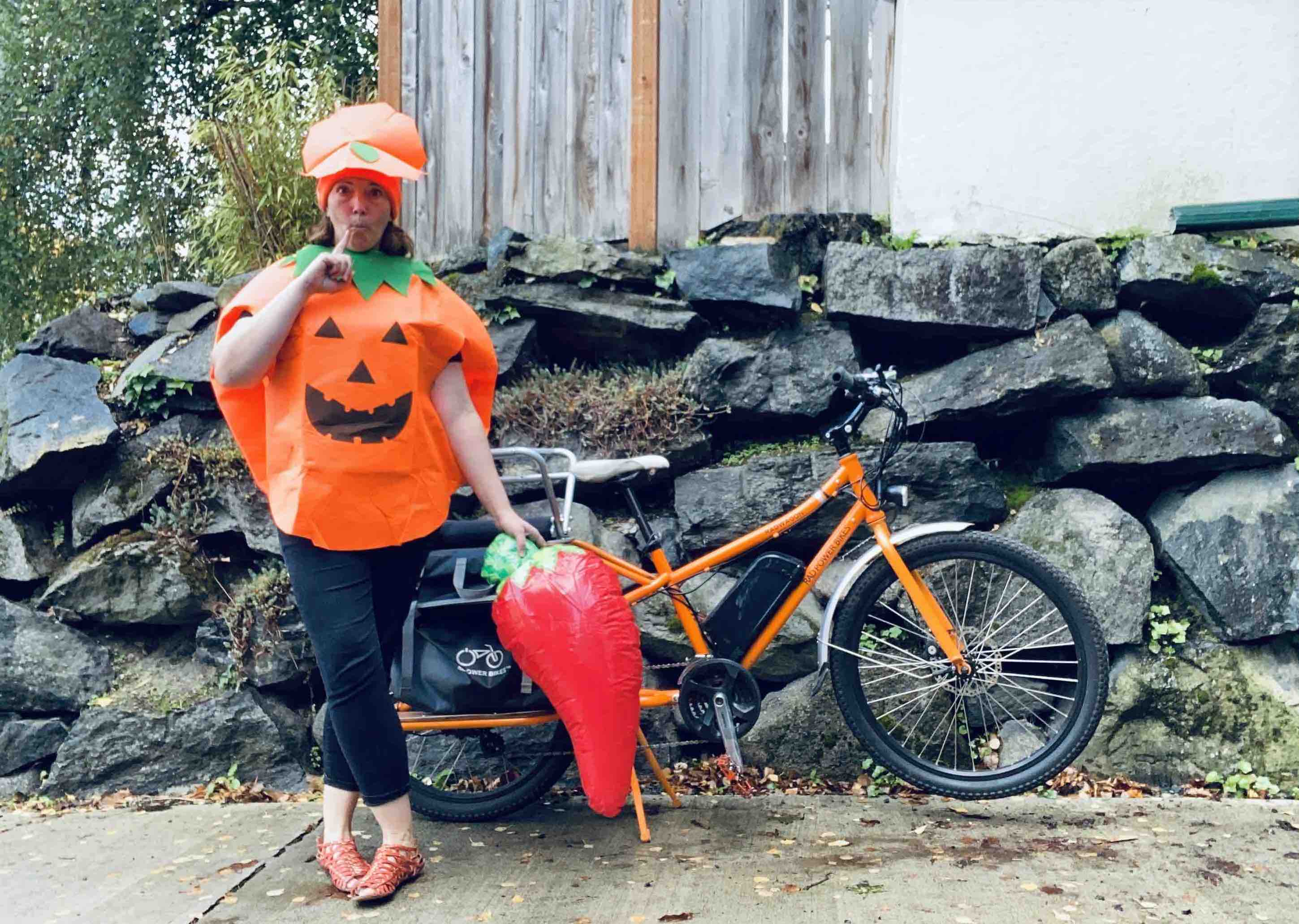 A woman dressed in a Halloween costume stands next to her RadWagon electric metro bike.