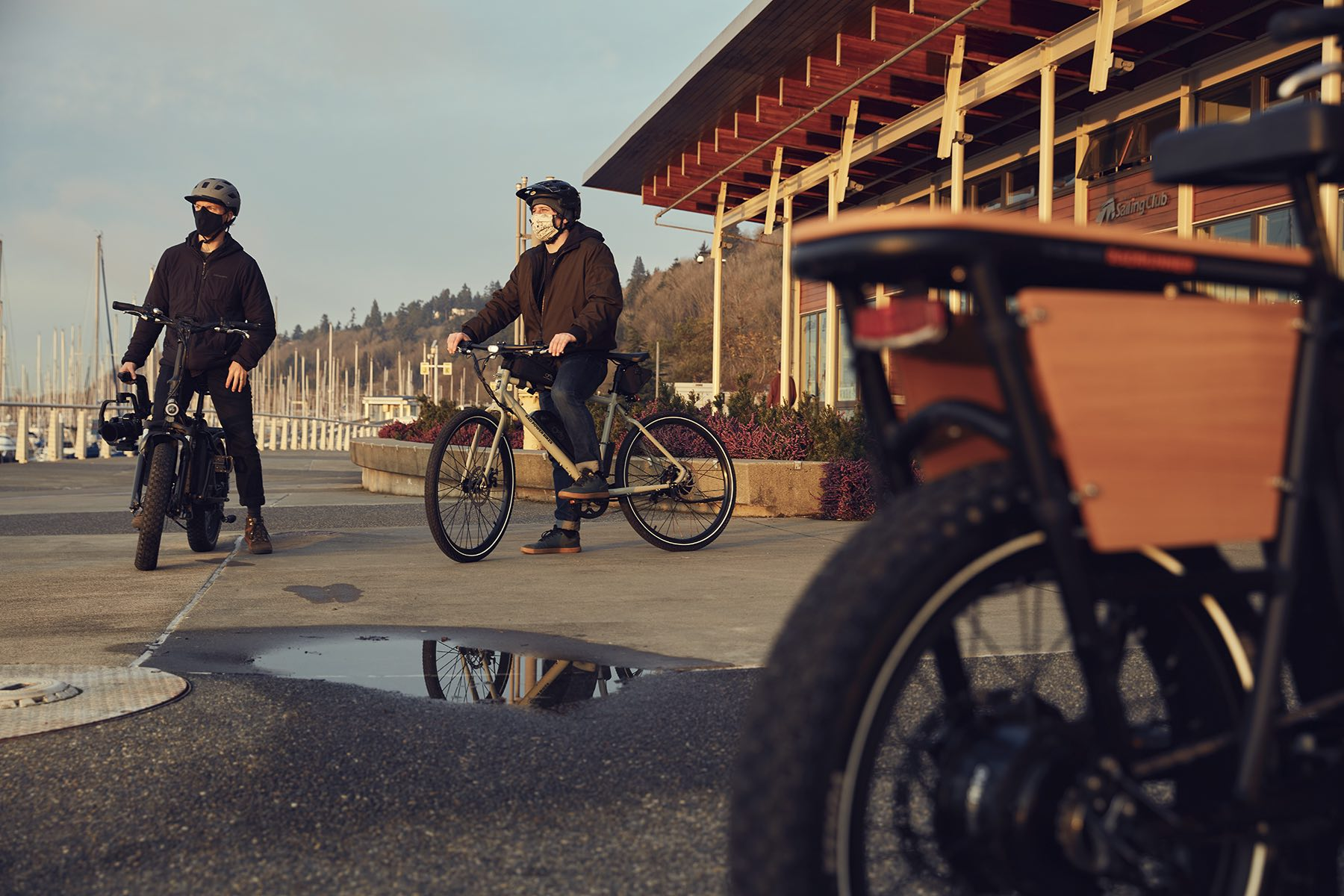 Three riders are on their electric bikes near a puddle