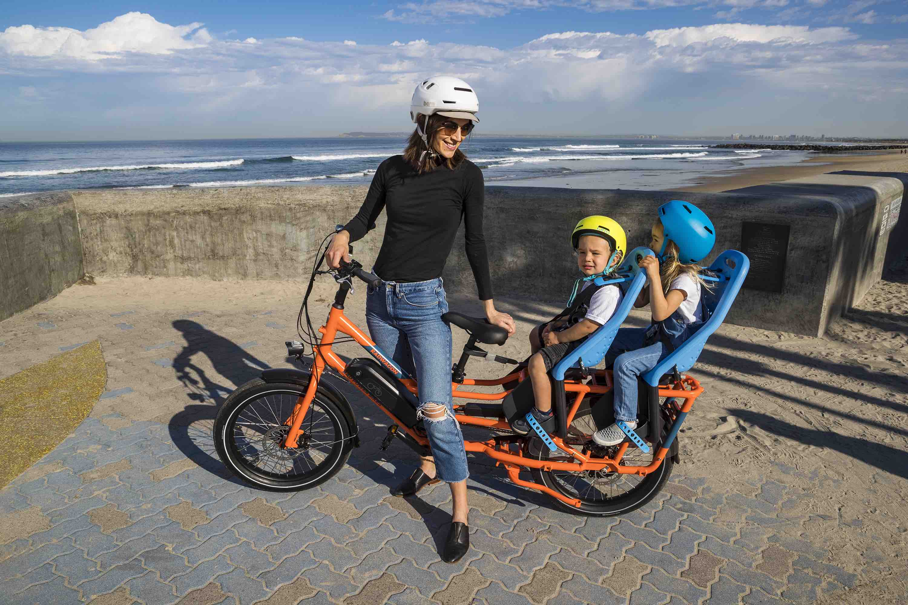 A woman rides her RadWagon by the San Diego coast with her children.