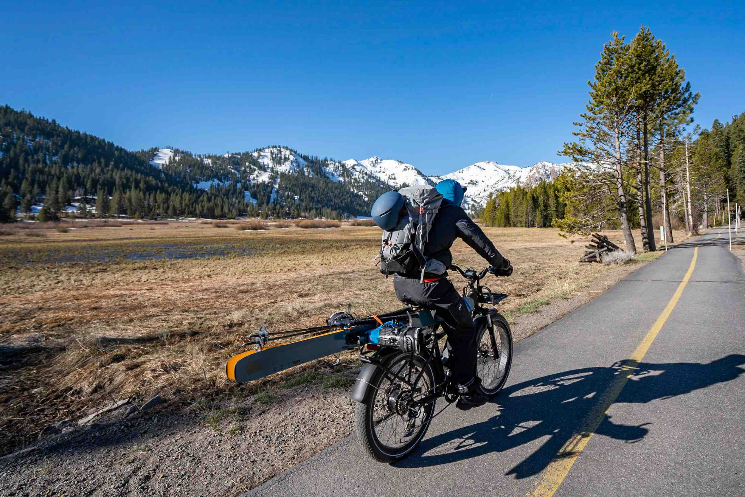A skier rides toward a mountain with a pair of skis affixed to his RadRover.