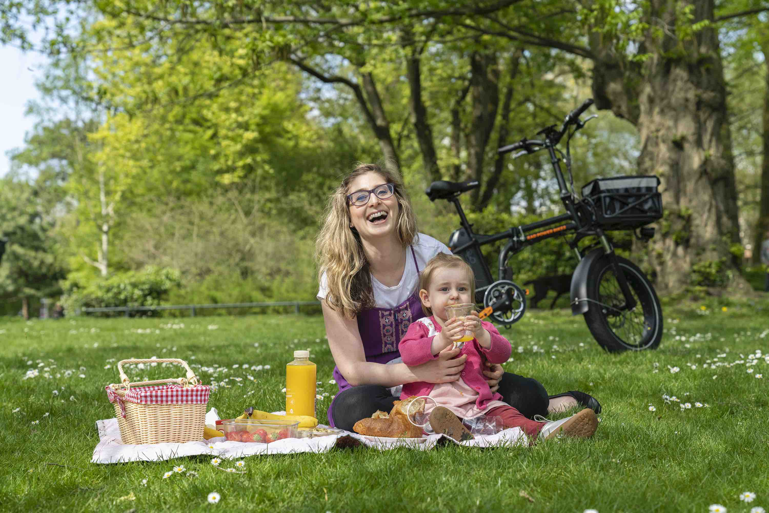 A woman and child enjoy a picnic alongside their electric bike.