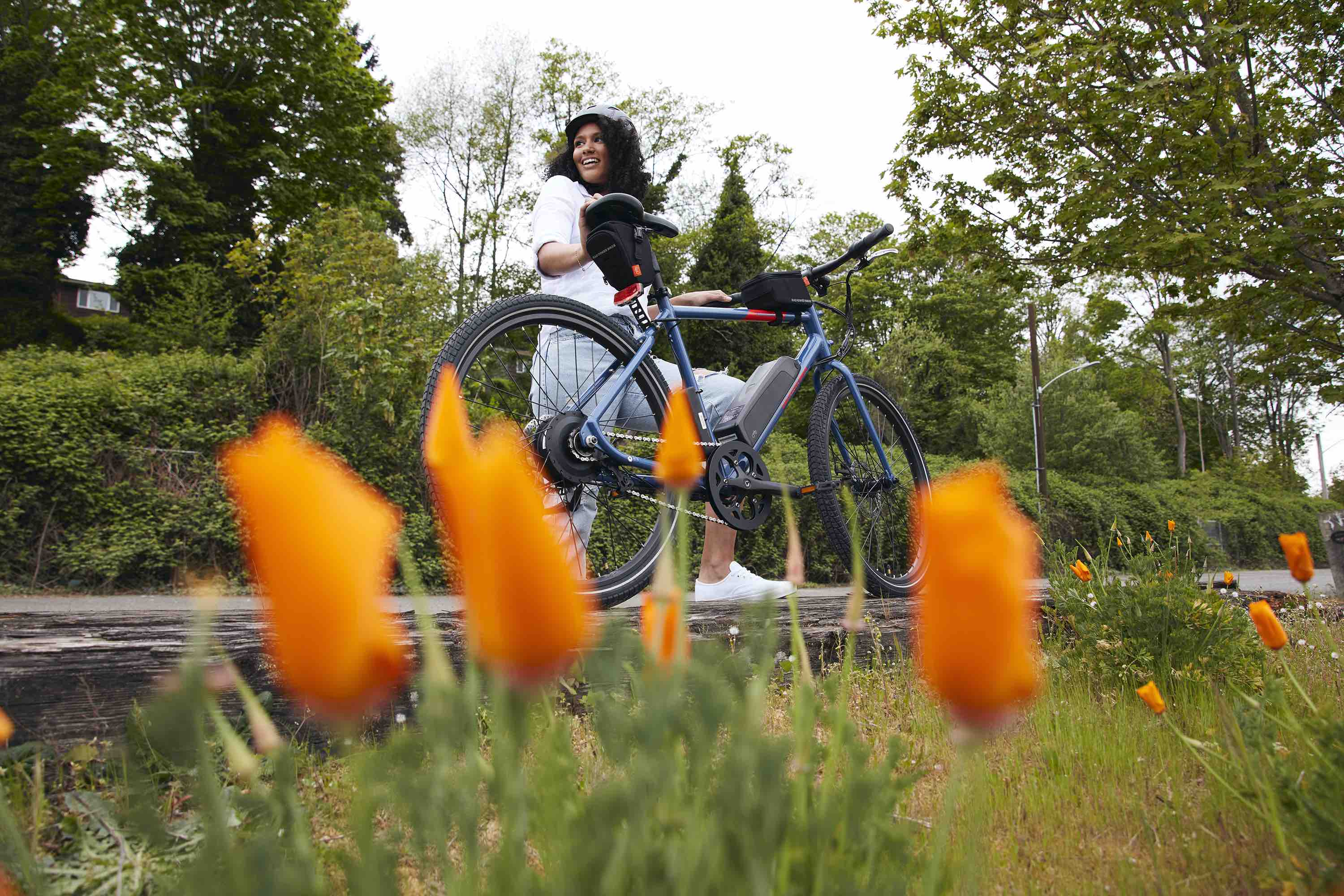 A woman poses next to her RadMission electric metro bike alongside spring flowers.