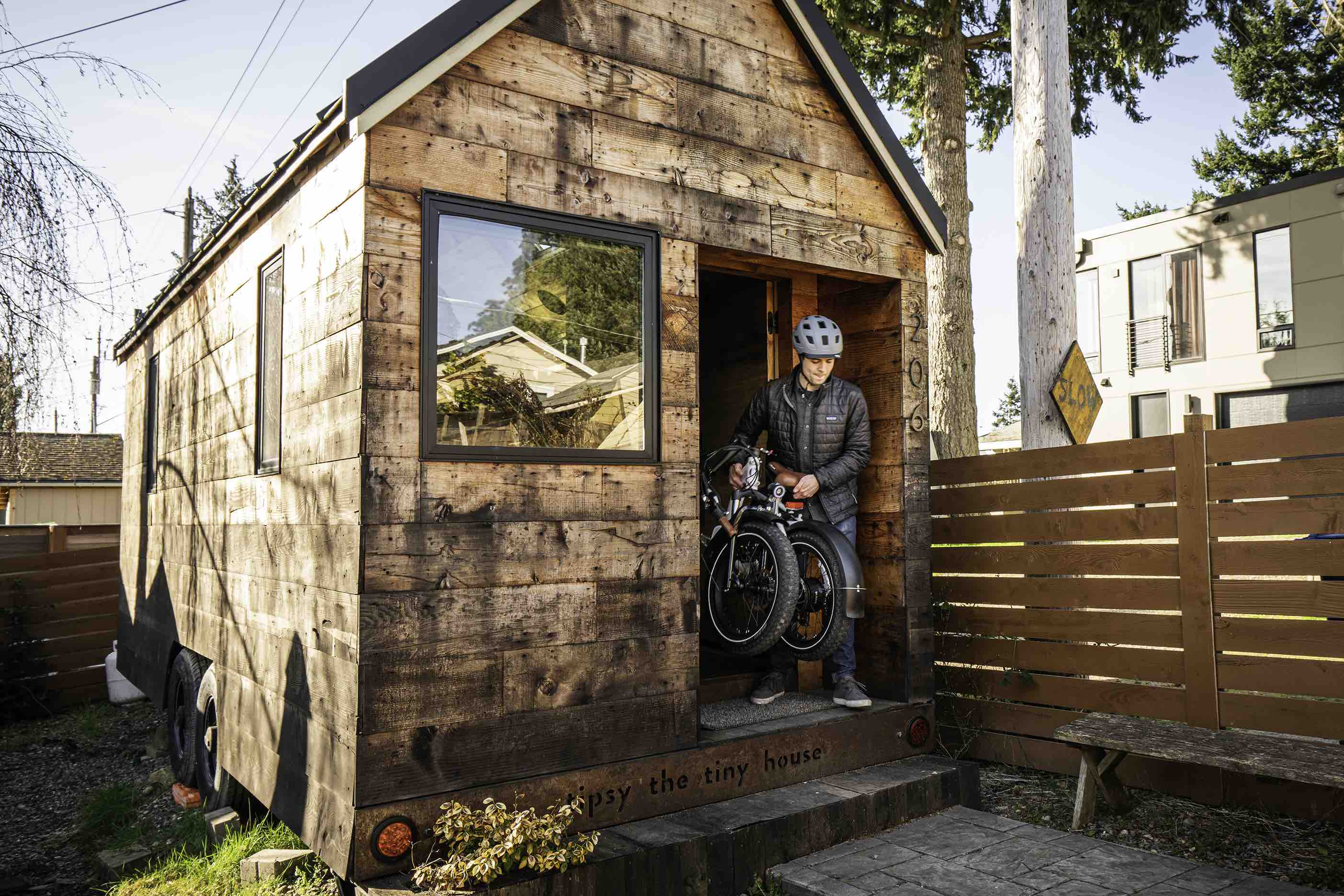 A man exits a tiny house with his RadMini electric folding bike.