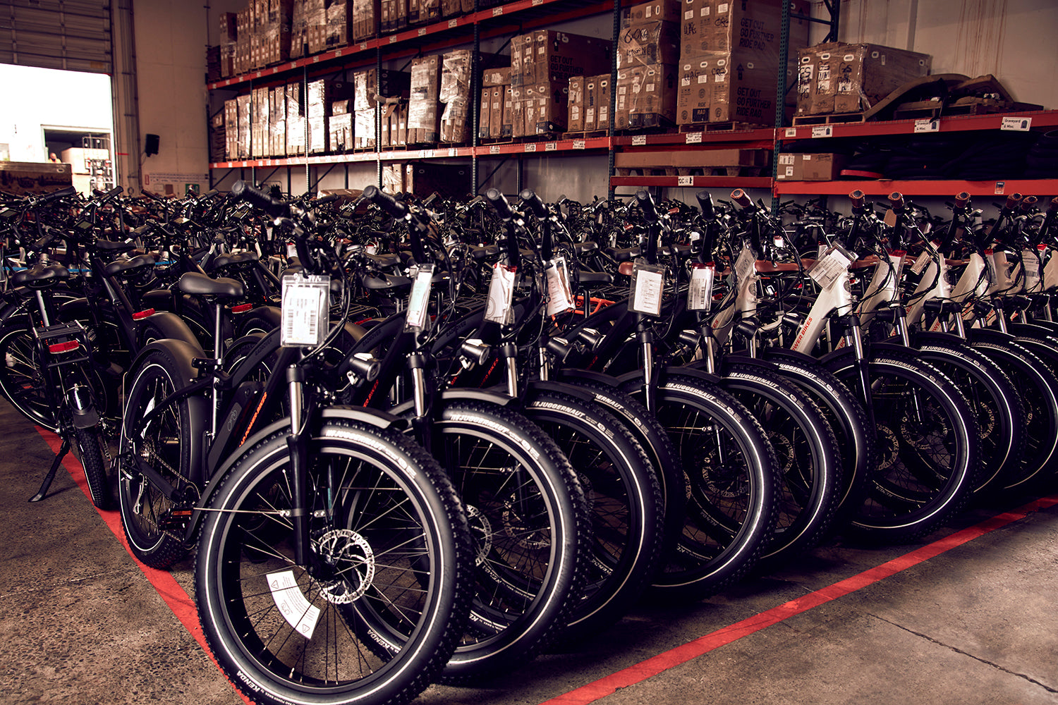 A row of electric bikes stacked alongside each other in a Rad Power Bikes warehouse.