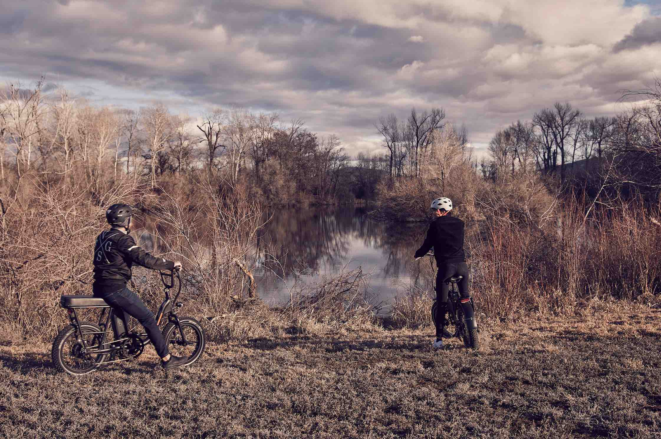 A man and woman ride their electric bikes to a pond.