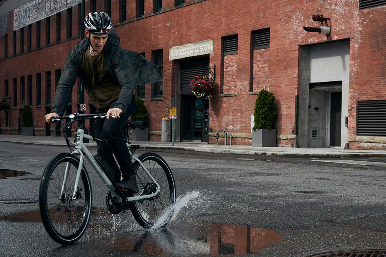 Person riding gray RadMission e-bike and splashing puddle