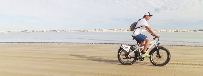 Person riding a RadRover on the beach