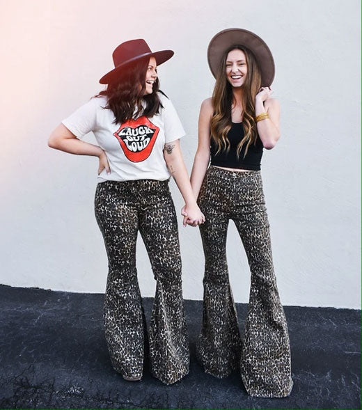 Two women wearing leopard print bell bottom pants