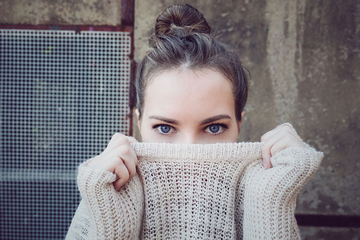 Woman with sweater pulled up over her nose