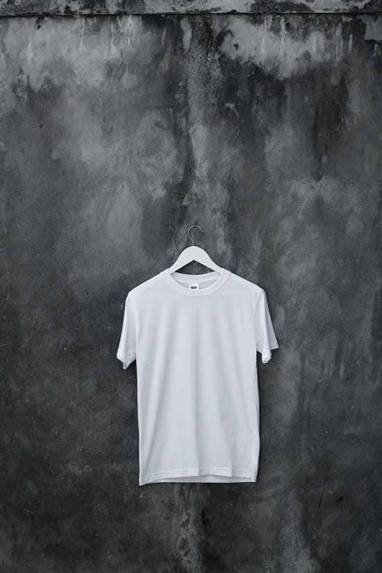 White t-shirt on a white hanger hanging against a grey background