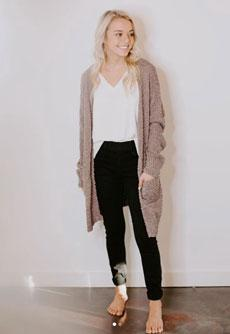 A blonde woman wearing a long cardigan and black pants)