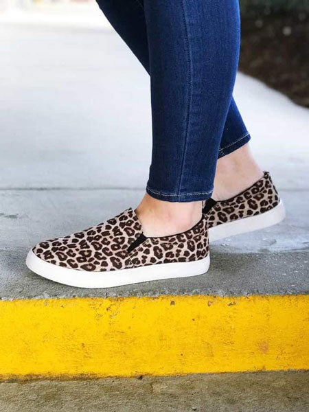 a pair of animal print slip-on shoes