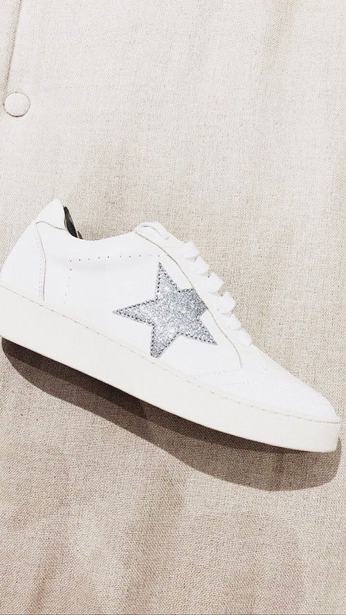 White low-top sneakers with a silver star