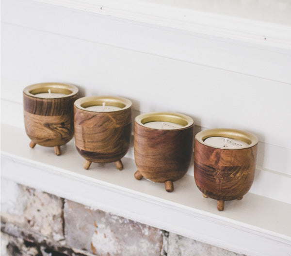 Row of four small wooden candles on a white shelf