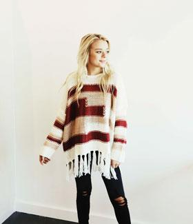 Blonde woman wearing a fringe over-sized sweater