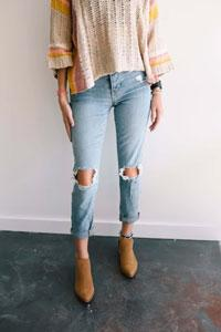 Woman wearing ripped denim jeans and brown boots