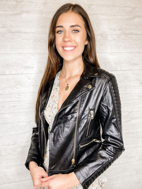 Smiling woman in black leather moto jacket