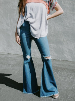 woman wearing super flared ripped denim jeans