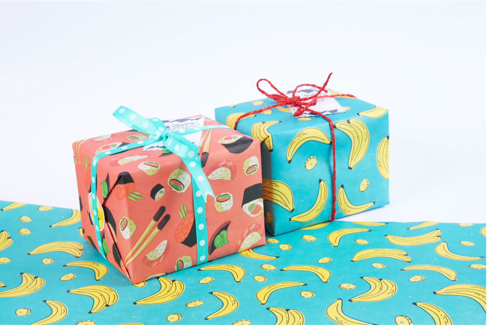 two gifts wrapped in sushi and banana-themed wrapping paper