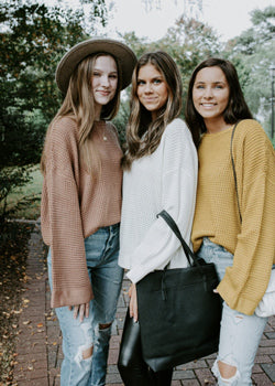 three women wearing jeans and different colored knit sweaters