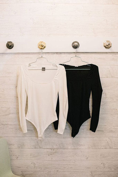 Two scoop neck bodysuits on hangers